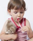 Jeune enfant en bas âge embrassant son édredon quand brushin Photos stock
