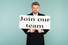 Jeune enseigne d'apparence d'homme d'affaires de barbe fâchée avec le signe joindre notre équipe photo stock