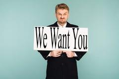Jeune enseigne d'apparence d'homme d'affaires de barbe fâchée avec le signe nous vous voulons photo libre de droits