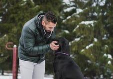 Jeune entraîneur de chien avec un Labrador noir en parc Photos stock