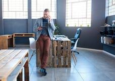 Jeune entrepreneur à l'aide d'un comprimé et parlant sur son téléphone portable photos stock