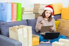 Jeune entrepreneur en ligne féminin asiatique de vendeur, chapeau de port de Noël, travaillant à ses affaires en ligne image stock