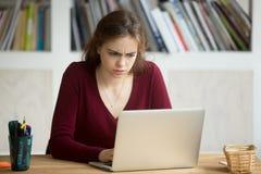Jeune entrepreneur féminin occasionnel perplexe regardant le thyristor d'ordinateur portable Photographie stock