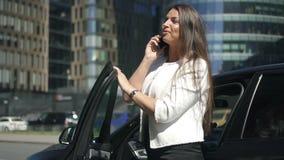 Jeune entrepreneur féminin parlant au téléphone tenant la voiture proche sur la rue de ville banque de vidéos