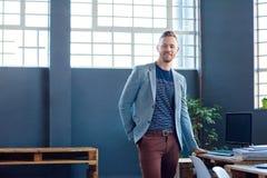 Jeune entrepreneur sûr seul se tenant dans un bureau moderne photos libres de droits