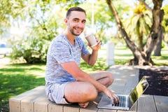 Jeune entrepreneur travaillant au parc dehors sur le banc en bois Homme à l'aide de l'ordinateur portable, écrivant le texte Vue  photo stock