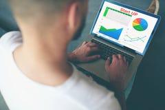 Jeune entrepreneur travaillant avec des données de statistiques sur le bureau moderne de carnet à l'intérieur Photo stock