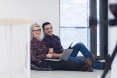 Jeune entreprise, couple travaillant sur l'ordinateur portable au bureau Images stock