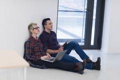 Jeune entreprise, couple travaillant sur l'ordinateur portable au bureau Photos stock