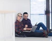 Jeune entreprise, couple travaillant sur l'ordinateur portable au bureau Image stock