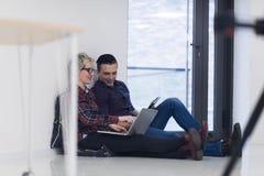Jeune entreprise, couple travaillant sur l'ordinateur portable au bureau Photographie stock