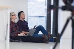 Jeune entreprise, couple travaillant sur l'ordinateur portable au bureau Images libres de droits