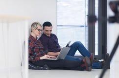 Jeune entreprise, couple travaillant sur l'ordinateur portable au bureau Photos libres de droits