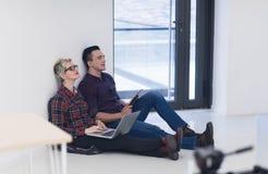 Jeune entreprise, couple travaillant sur l'ordinateur portable au bureau Photographie stock libre de droits