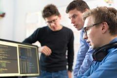 Jeune entreprise, programmateur de logiciel travaillant sur l'ordinateur de bureau Images libres de droits