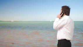 Jeune entretien d'homme d'affaires sur le t?l?phone portable pr?s de la mer banque de vidéos