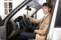 jeune essai exécutif fier son véhicule neuf sur la route Photos stock
