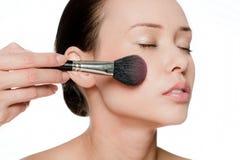 Jeune et attirant femme appliquant le blusher Photographie stock