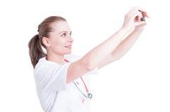 Jeune et attirant médecin ou médecin féminin prenant un selfie Images libres de droits