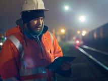 Jeune et beau travailleur à l'aide du comprimé pendant le hignt Dans le casque et la veste réfléchie Image libre de droits