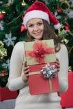 Jeune et belle femme caucasienne en chapeau et cadeau rouges de se tenir photo stock