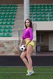 Jeune et belle femme de forme physique posant sur le terrain de jeu photo libre de droits