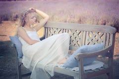 Jeune et belle femme s'asseyant sur un banc Photographie stock libre de droits
