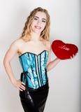 Jeune et belle fille bouclée dans le corset bleu tenant un oreiller rouge de coeur Photo stock