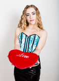 Jeune et belle fille bouclée dans le corset bleu tenant un oreiller rouge de coeur Image stock