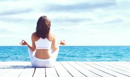 Jeune et belle fille dans les vêtements de sport blancs faisant le yoga sur un courtiser Photographie stock libre de droits