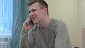 Jeune et en bonne santé homme souriant et parlant au téléphone intelligent à la maison Photographie stock libre de droits