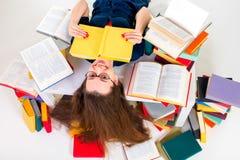 Jeune et futée fille se trouvant avec le livre entouré par le livre coloré Photos stock