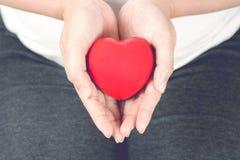 Jeune et heureuse femme enceinte jugeant le coeur rouge d'amour disponible dedans Photos libres de droits