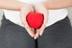 Jeune et heureuse femme enceinte jugeant le coeur rouge d'amour disponible dedans Image stock
