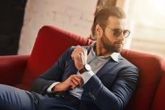 Jeune et réussi L'homme d'affaires s'assied sur le sofa dans le bureau moderne et regarde loin par des lunettes de soleil photos stock