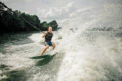 Jeune et sportif homme wakesurfing sur le conseil contre le ciel photographie stock