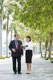 Jeune exécutif féminin asiatique et homme d'affaires supérieur marchant ensemble Image libre de droits