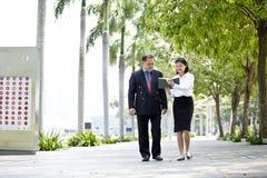 Jeune exécutif féminin asiatique et homme d'affaires supérieur marchant ensemble Images libres de droits
