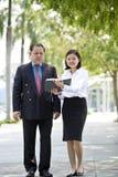 Jeune exécutif féminin asiatique et homme d'affaires supérieur marchant ensemble Photographie stock libre de droits