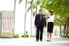 Jeune exécutif féminin asiatique et homme d'affaires supérieur marchant ensemble Photographie stock