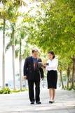 Jeune exécutif féminin asiatique et homme d'affaires supérieur marchant ensemble Image stock