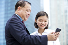 Jeune exécutif féminin asiatique et homme d'affaires supérieur utilisant le téléphone intelligent Images libres de droits