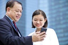 Jeune exécutif féminin asiatique et homme d'affaires supérieur utilisant le téléphone intelligent Photographie stock libre de droits