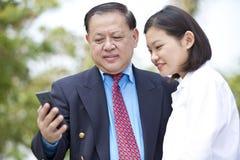 Jeune exécutif féminin asiatique et homme d'affaires supérieur utilisant le téléphone intelligent Photo stock