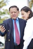 Jeune exécutif féminin asiatique et homme d'affaires supérieur utilisant le téléphone intelligent Photographie stock