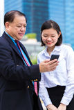 Jeune exécutif féminin asiatique et homme d'affaires supérieur utilisant le téléphone intelligent Image libre de droits
