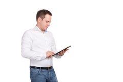 Jeune exécutif masculin sérieux à l'aide du comprimé numérique sur le fond blanc Photos libres de droits