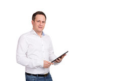 Jeune exécutif masculin sérieux à l'aide du comprimé numérique sur le fond blanc, regardant l'appareil-photo Photographie stock libre de droits