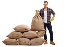 Jeune exploitant agricole se tenant à côté de la pile des sacs et tenant la toile de jute s Images libres de droits