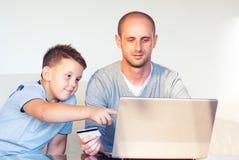 Jeune faher avec l'enfant achetant en ligne à la maison images libres de droits